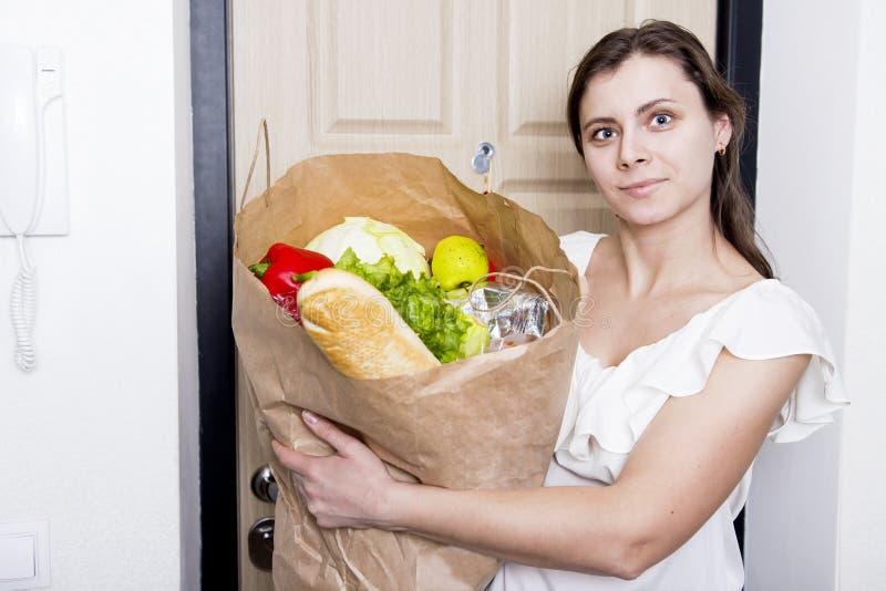 Девушка пришла домой с пакетом еды молодая женщина принесенная домой от овощей гастронома Приобретение продуктов стоковая фотография
