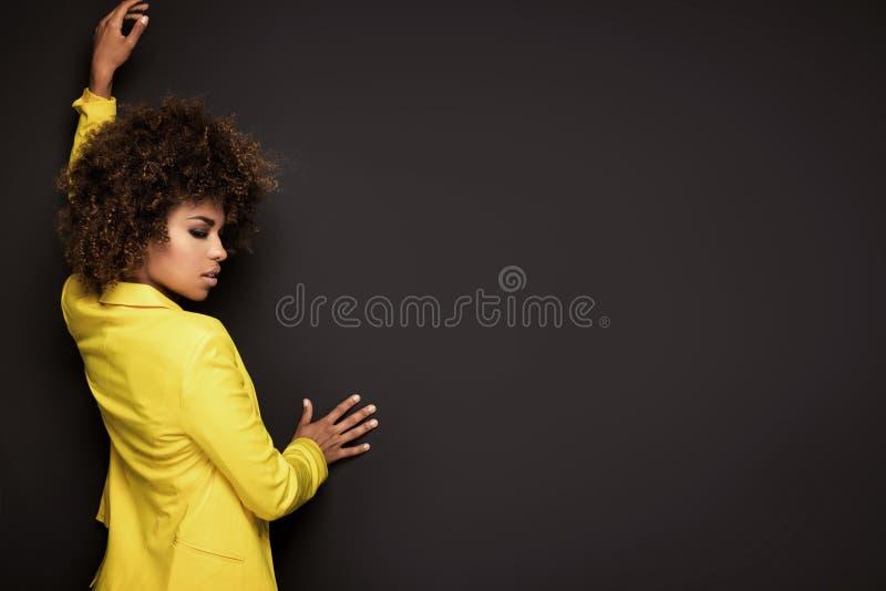 Девушка при афро стиль причёсок представляя в желтой куртке стоковое изображение