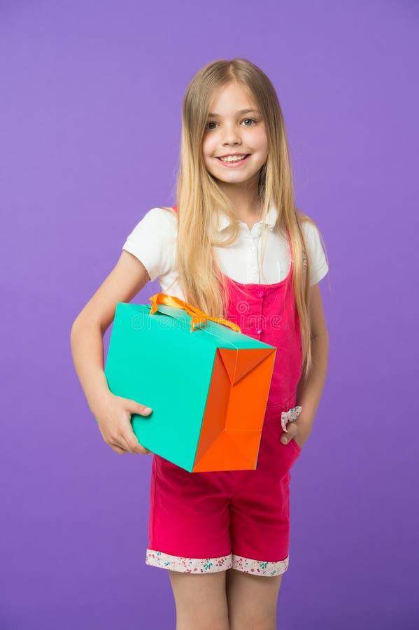 Девушка при большая улыбка держа красочную бумажную сумку Модель с оранжевой и зеленой подарочной коробкой Ребенок с длинный носи стоковое изображение rf