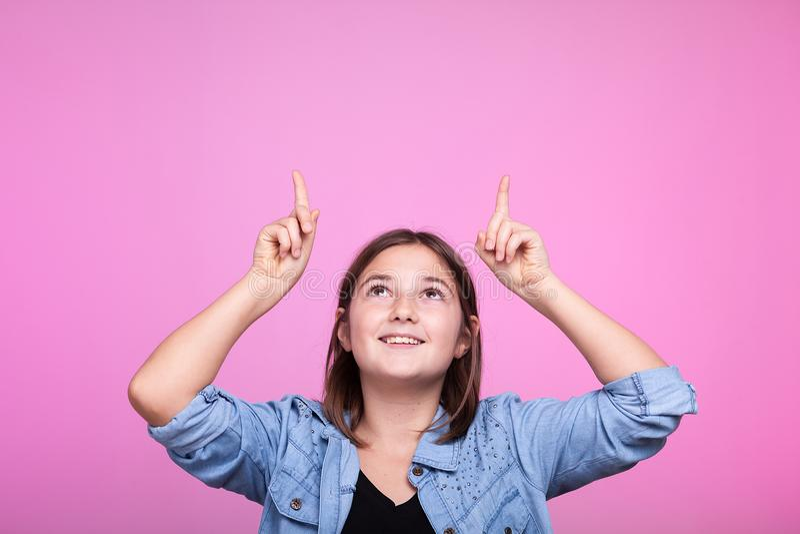 Девушка при ее руки вверх poiting в воздухе стоковое изображение rf