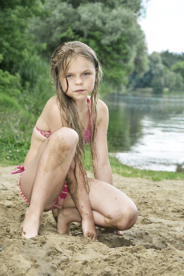 Девушка при длинные волосы сидя на песке на пляже около Ла стоковое изображение rf