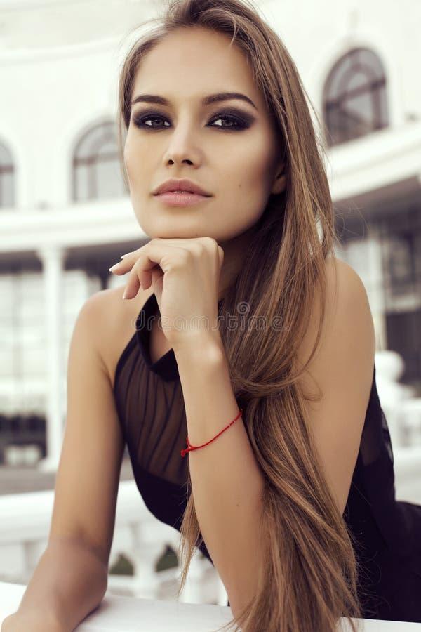 Девушка при длинные прямые волосы нося элегантное черное платье стоковое изображение
