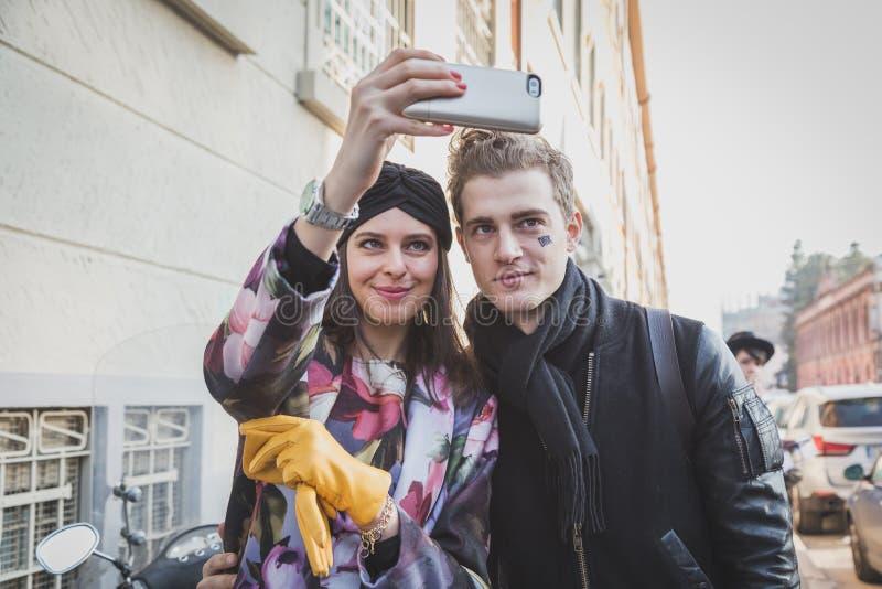 Девушка при модель принимая selfie вне здания модного парада Dirk Bikkembergs на неделя 2015 моды людей милана стоковое изображение