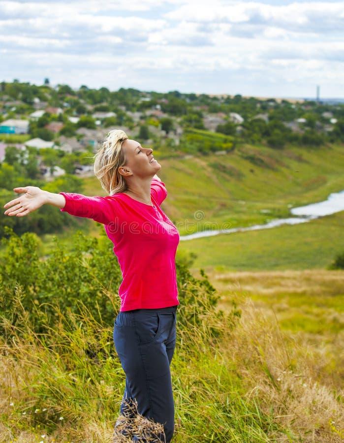 Девушка при оружия поднятые в ветре стоковое изображение rf