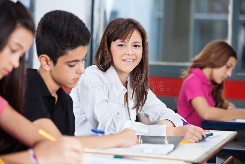 Девушка при одноклассники сидя на столе в классе стоковое фото rf