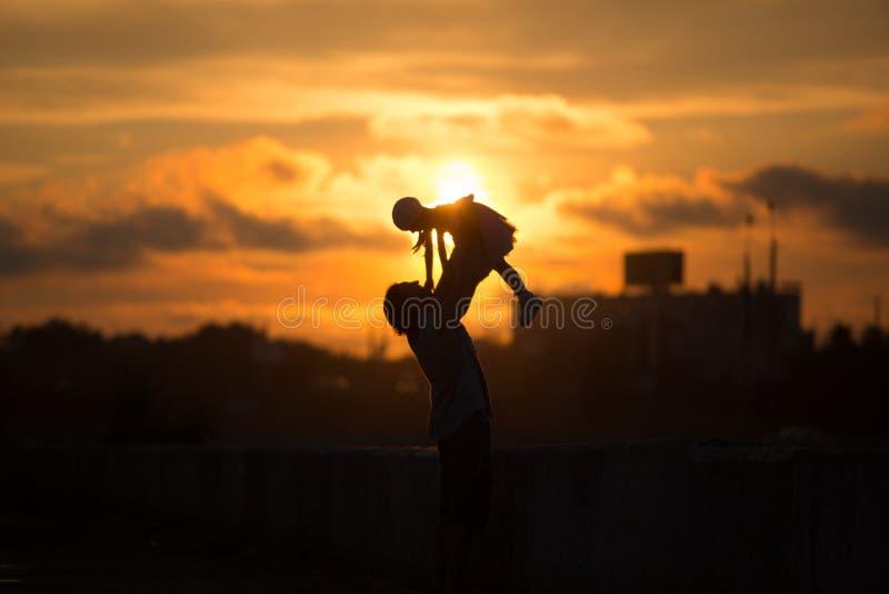 Девушка при папа идя в силуэт захода солнца стоковая фотография