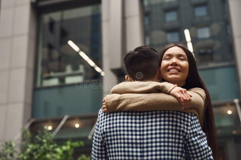Девушка при парень romantically обнимая на предпосылке здания стоковое фото