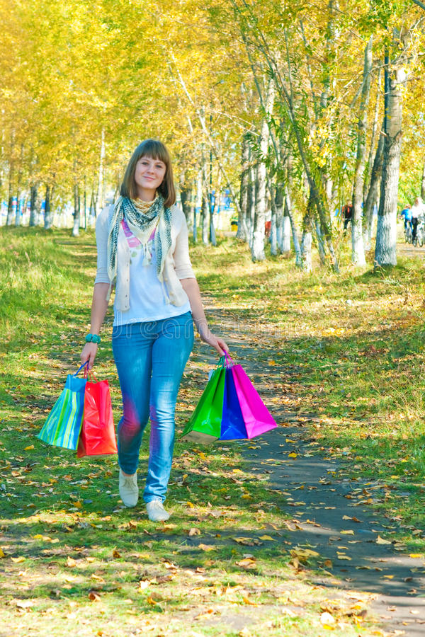 Девушка при пестротканые пакеты идя на парк стоковое изображение