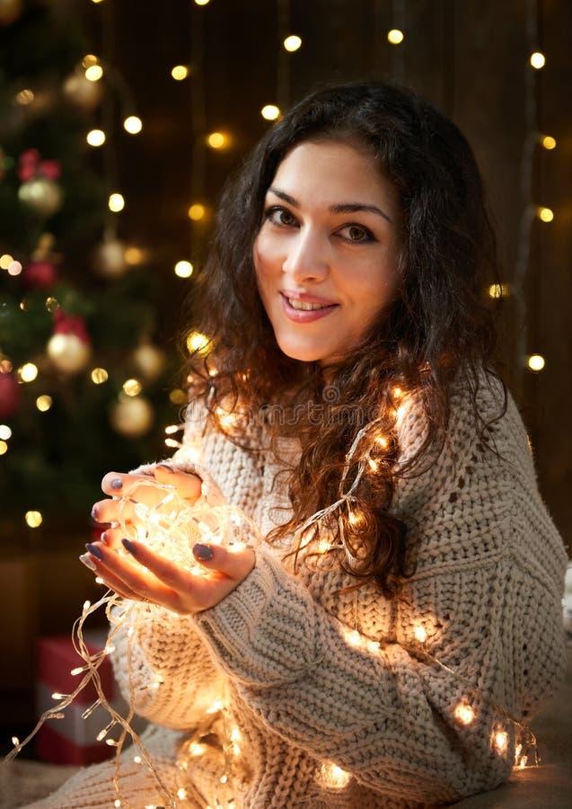 Девушка при пригорошня светов рождества, одетая в белом свитере, темная деревянная предпосылка, концепция зимнего отдыха стоковые фотографии rf