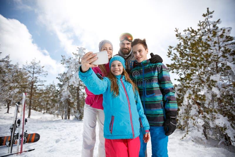 Девушка при семья принимая фото с сотовым телефоном стоковое изображение