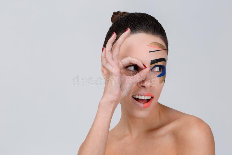 Девушка при творческий состав смотря к стороне и владениям индексу и большому пальцу руки около глаза Серая предпосылка стоковые изображения rf