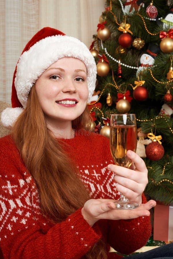 Девушка при шампанское одетое как santa в украшении рождества дома Концепция кануна Нового Годаа и зимнего отдыха стоковое фото