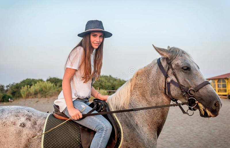 Девушка при шляпа ехать лошадь стоковая фотография