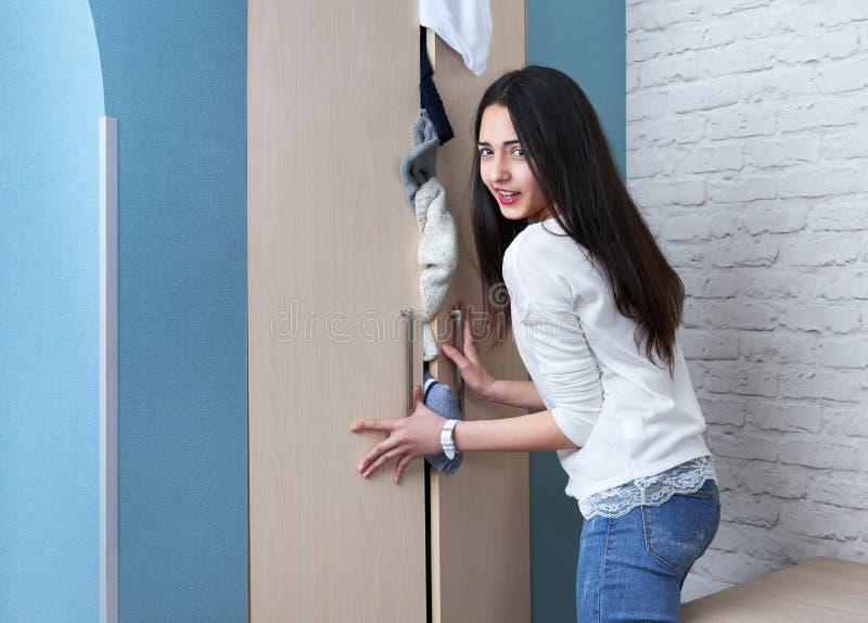 Девушка пробуя закрыть полный шкаф стоковые изображения rf
