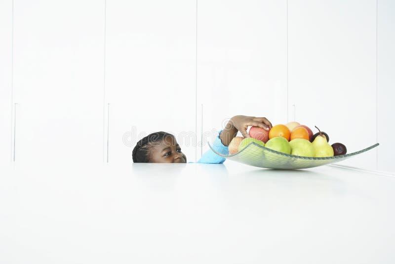 Девушка пробуя достигнуть плодоовощи в тарелке стоковые фото