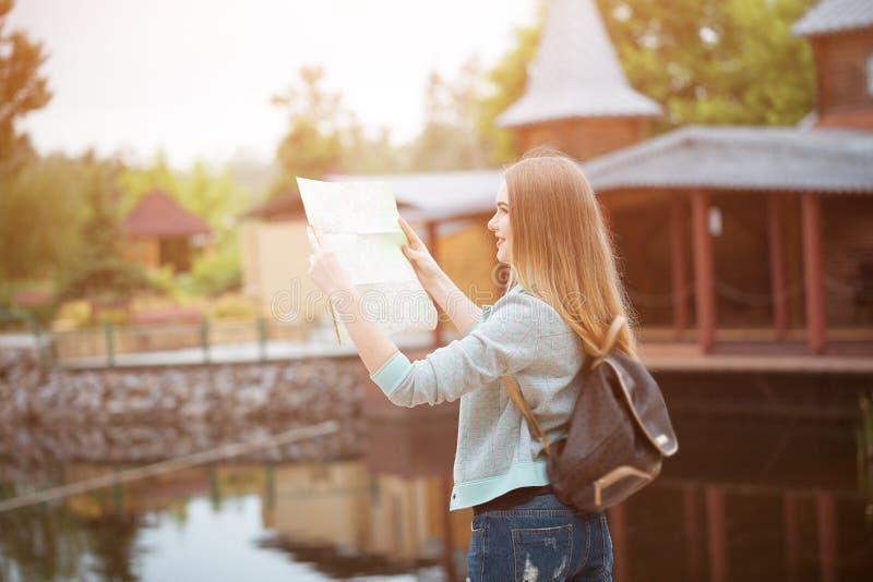 Девушка путешественника ища правильное направление на карте, оранжевом свете захода солнца, путешествуя вдоль Европы стоковое фото