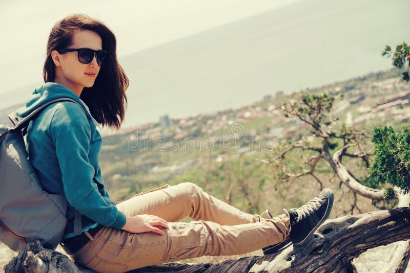 Девушка путешественника отдыхая на дереве стоковое изображение