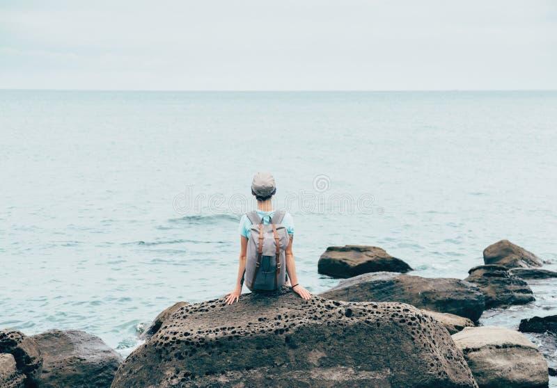 Девушка путешественника отдыхая на каменном побережье стоковые фотографии rf