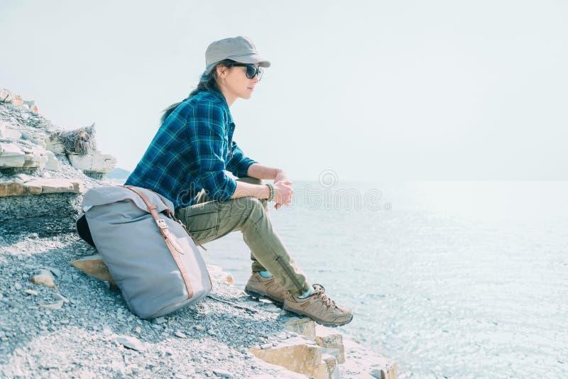 Девушка путешественника отдыхая на побережье стоковая фотография rf