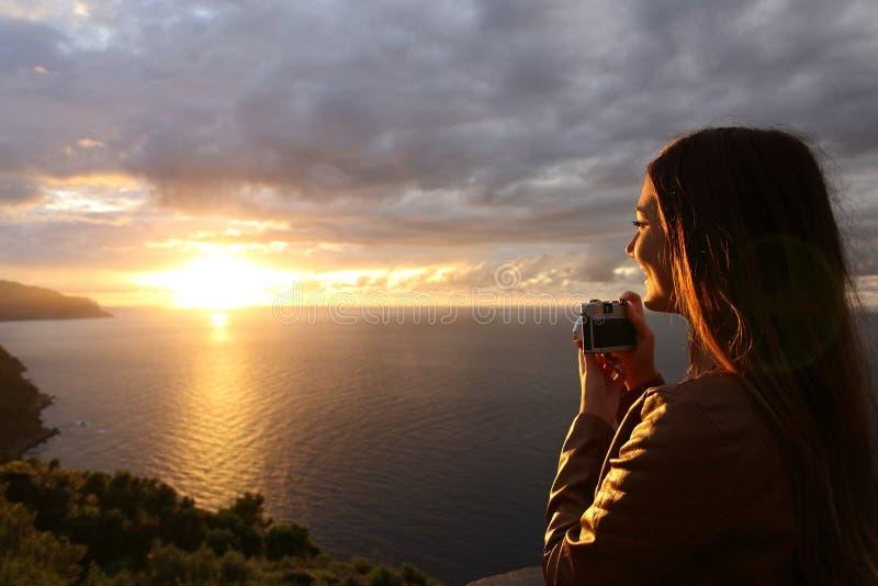 Девушка путешественника туристская принимая фото в заходе солнца на каникулах стоковые изображения rf