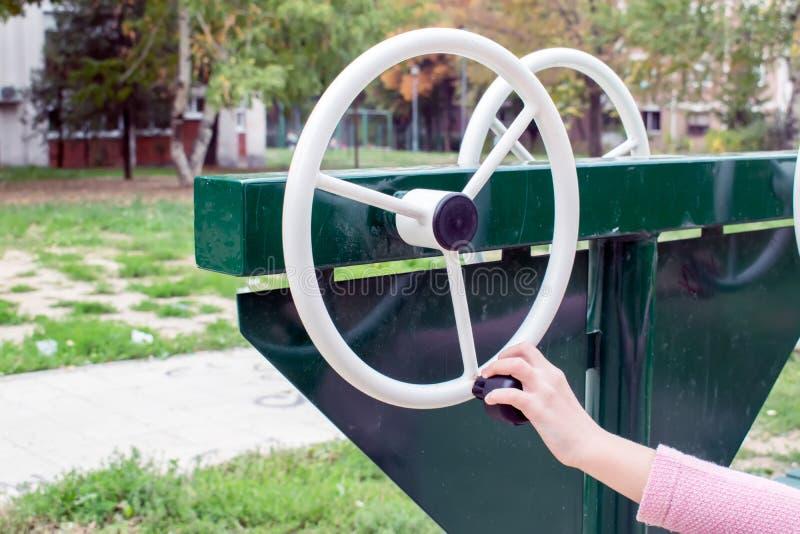 Девушка работая на оборудовании спортивной площадки спортзала outdoors стоковое фото