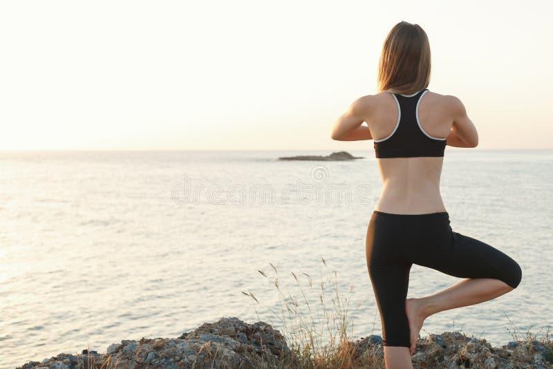 Девушка размышляя на пляже на заходе солнца стоковое фото rf
