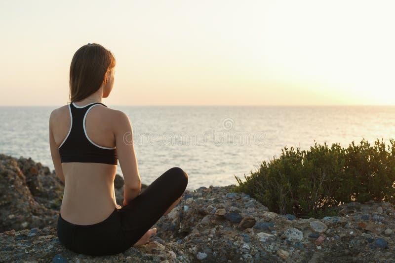 Девушка размышляя на пляже на заходе солнца стоковая фотография