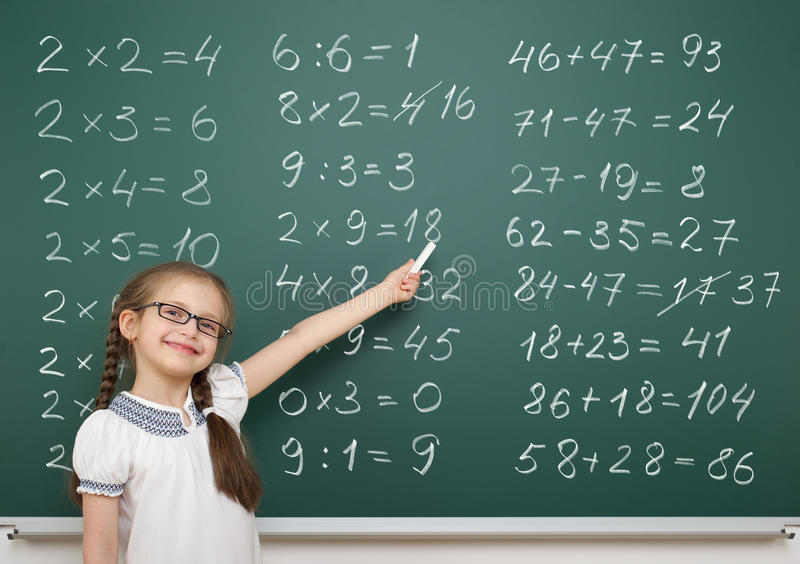 Девушка разрешает математику на школьном правлении стоковое изображение