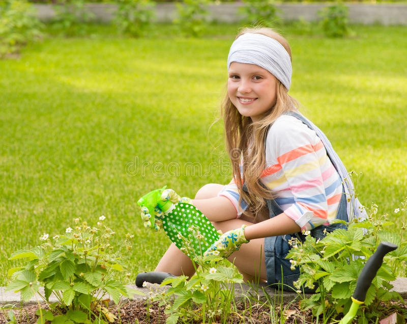 Девушка распыляет заводы в саде стоковые фото
