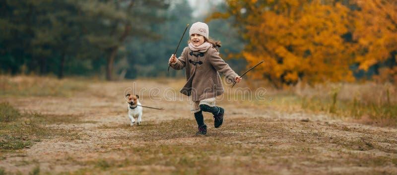 Девушка ребенка бежит и играет с его собакой во время прогулки стоковая фотография rf
