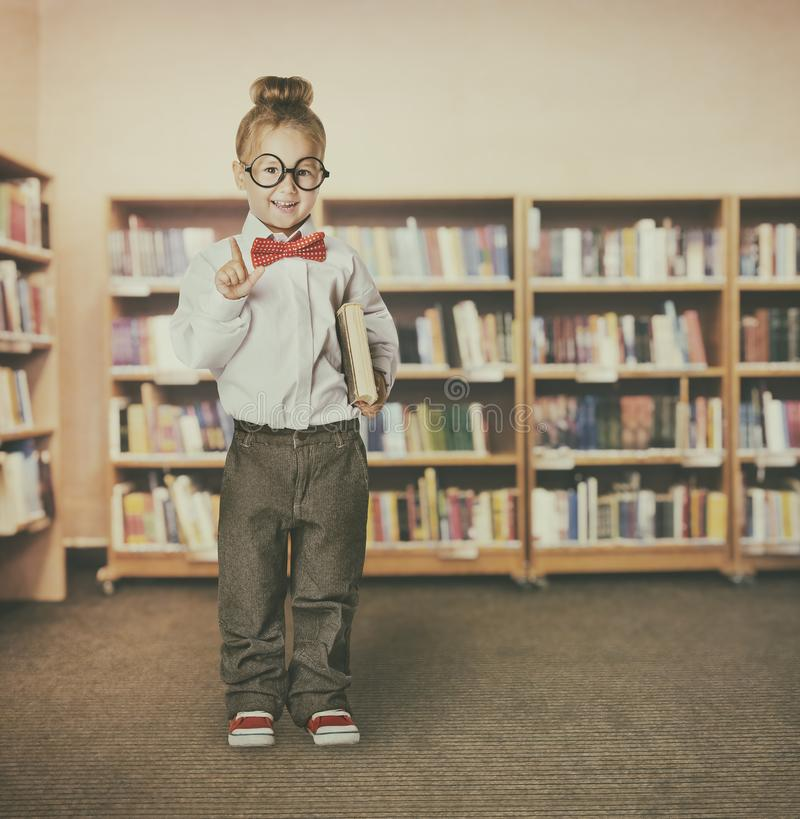 Девушка ребенка в книгах удерживания школьной библиотеки, указывая умный ребенк стоковые изображения rf