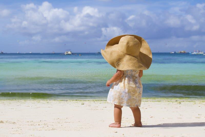Девушка ребенка в шлеме лета на тропической предпосылке моря стоковые фото