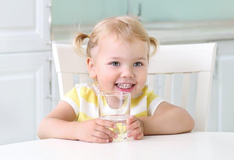 Девушка ребенка держа стекло воды, уклада жизни питания ребенк здорового стоковые изображения