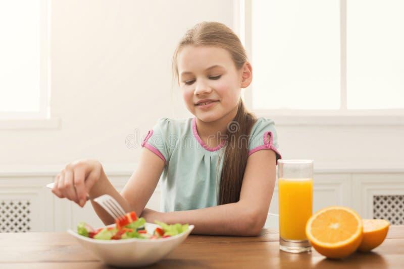 Девушка ребенка есть свежий салат и выпивая апельсиновый сок стоковые изображения rf