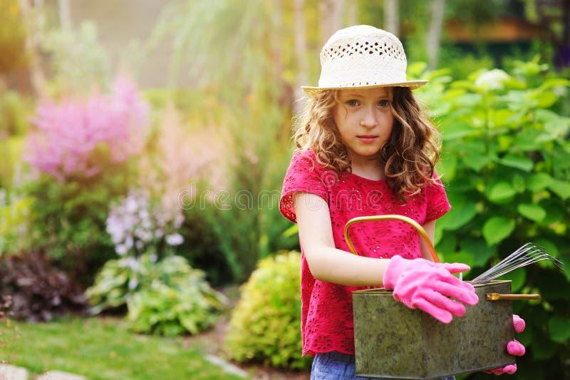 Девушка ребенка играя маленький садовника и помогая в саде лета, нося шляпе и перчатках стоковая фотография rf