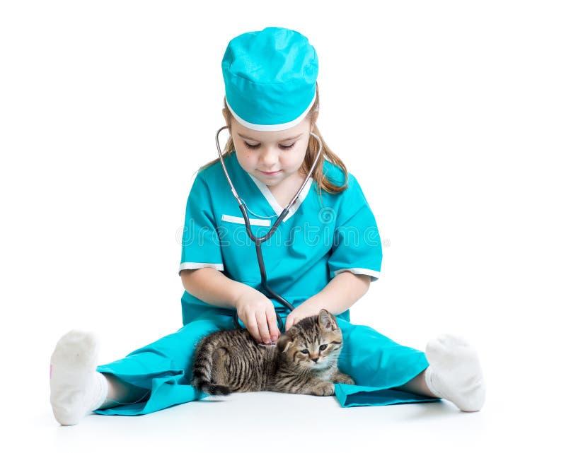 Девушка ребенка играя доктора при изолированный кот стоковые фото