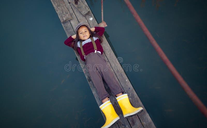 Девушка ребенка лежит на деревянном мосте и улыбках на предпосылке riv стоковое изображение rf