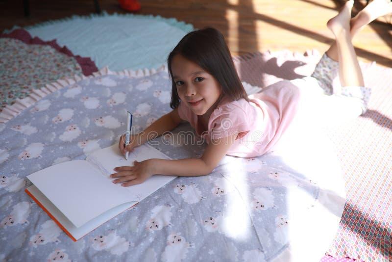 Девушка ребенка лежит на циновке и рисует стоковое изображение rf