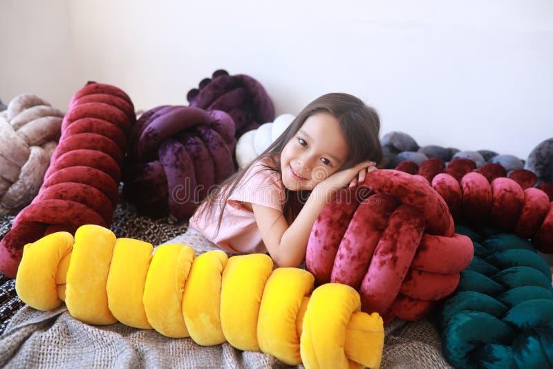 Девушка ребенка лежит среди необыкновенных подушек в пижамах стоковое изображение