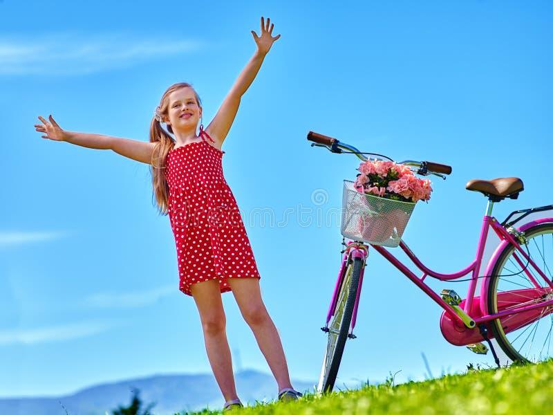 Девушка ребенка нося красные точки польки одевает велосипед езд стоковое изображение