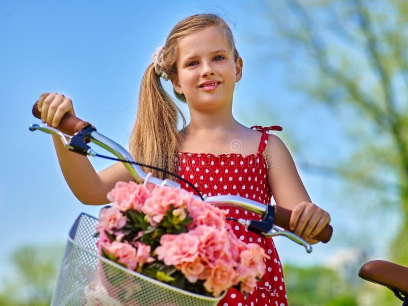 Девушка ребенка нося красные точки польки одевает велосипед езд стоковая фотография