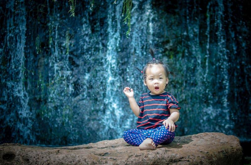 Девушка ребенка поднимает ее руку сидя на утесе стоковое фото