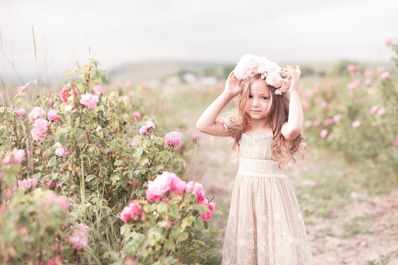 Девушка ребенка представляя в розарии стоковое изображение
