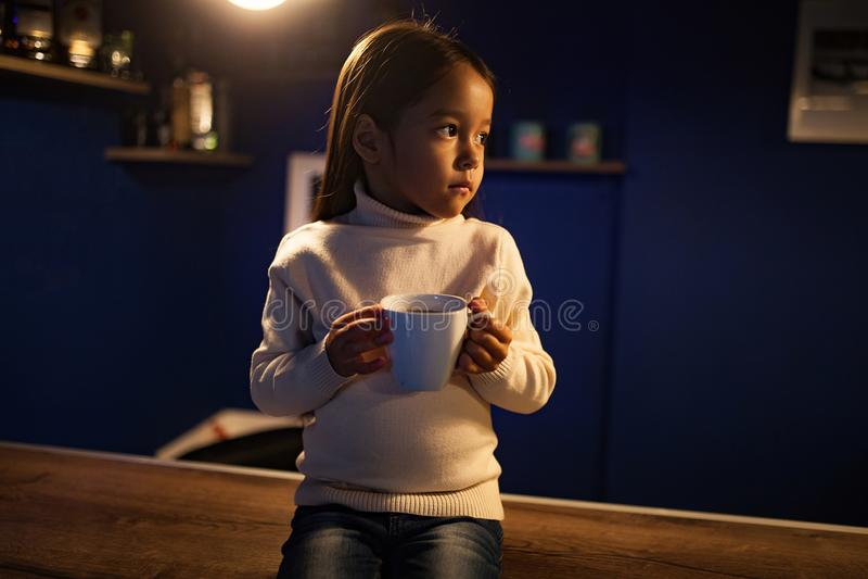 Девушка ребенка сидит загоренный электрической лампочкой с чашкой чаю в h стоковые изображения