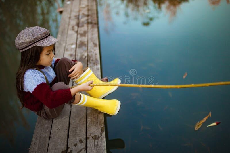 Девушка ребенка сидит на деревянном удя мосте и улавливает рыб с s стоковое изображение