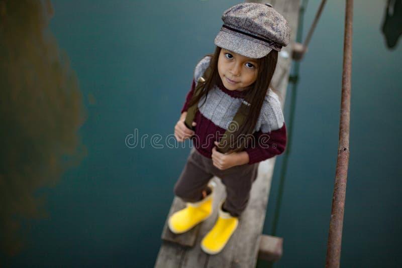 Девушка ребенка стоит на деревянном мосте и улыбках на предпосылке r стоковая фотография