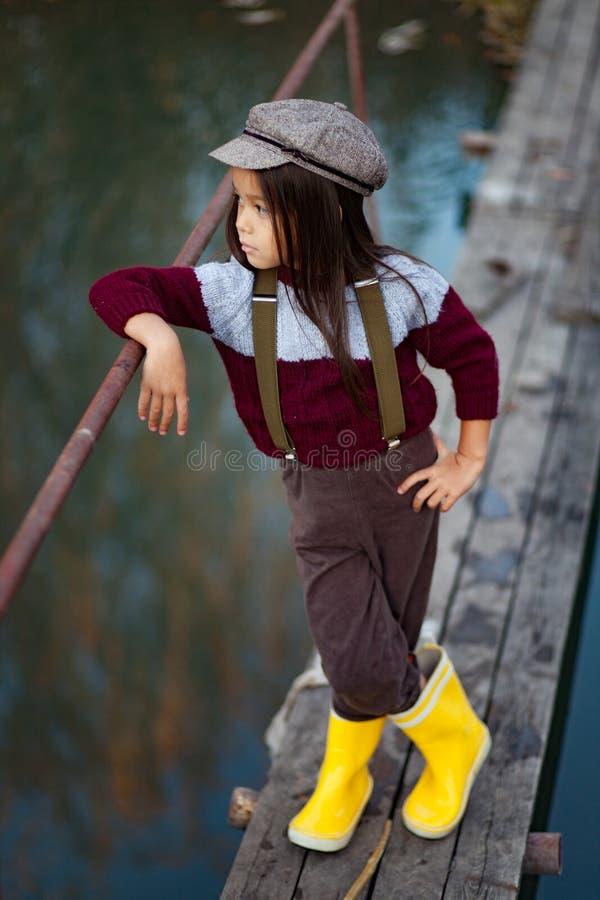 Девушка ребенка стоит на деревянном мосте на предпосылке реки стоковое фото rf