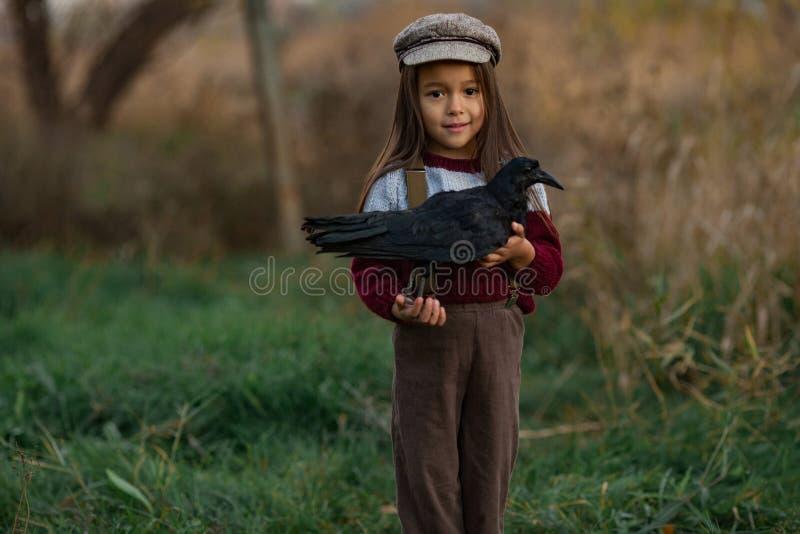 Девушка ребенка стоит с вороном в ее руках на предпосылке зеленого цвета стоковая фотография rf