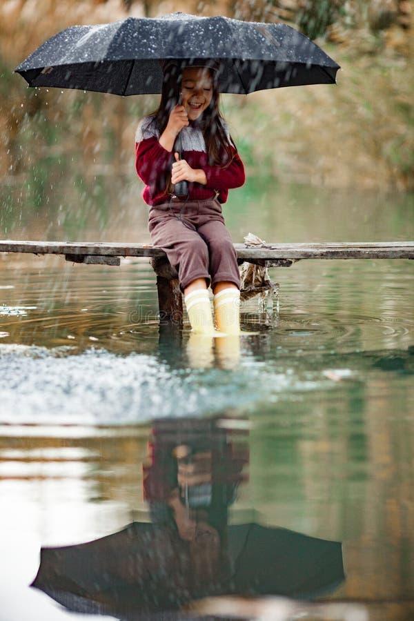 Девушка ребенка с зонтиком сидит на деревянном мосте и laughes в Ра стоковое фото rf