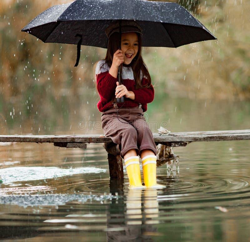 Девушка ребенка с зонтиком сидит на деревянном мосте и laughes в Ра стоковые изображения